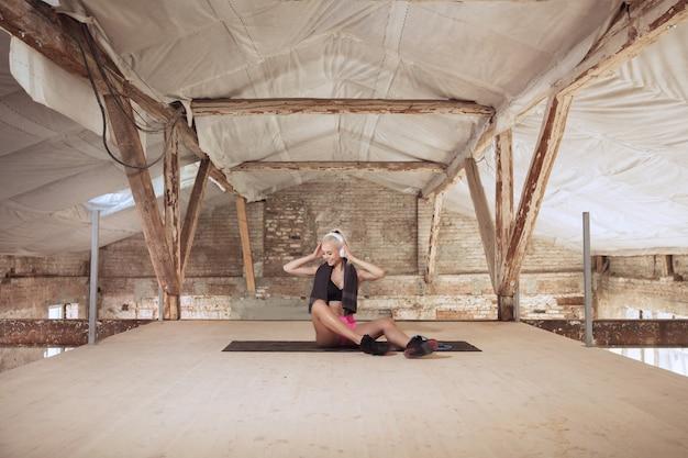 Een jonge atletische vrouw in witte koptelefoon traint het luisteren naar de muziek op een verlaten bouwplaats Gratis Foto
