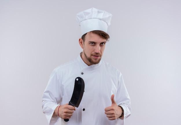 Een jonge, bebaarde chef-kokmens in wit uniform die vleesmes houdt en duimen toont terwijl hij op een witte muur kijkt Gratis Foto