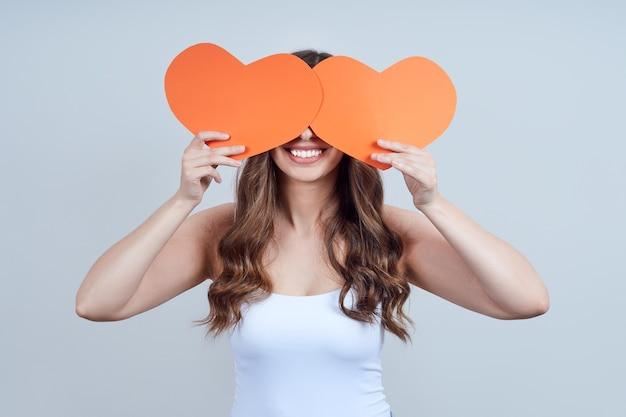 Een jonge blondine in een wit t-shirt bedekte haar gezicht met rode papieren hartjes. fijne valentijnsdag. wereldhartdag. Premium Foto