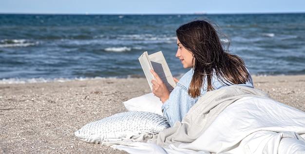 Een jonge brunette vrouw ligt aan zee op het strand bedekt met een deken, en leest een boek. de gezellige sfeer op het strand, zomerconcept. Gratis Foto