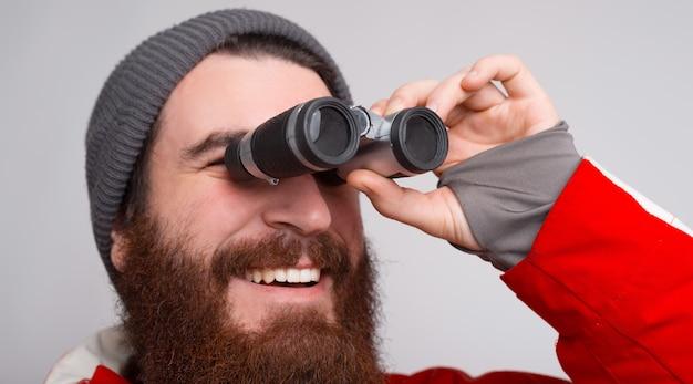 Een jonge en bebaarde klimmer kijkt door een verrekijker en lacht. Premium Foto