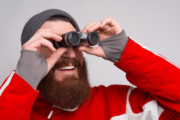 Een jonge en bebaarde klimmer lacht en kijkt door een verrekijker. een man met winterkleren kijkt ernaar uit. Premium Foto