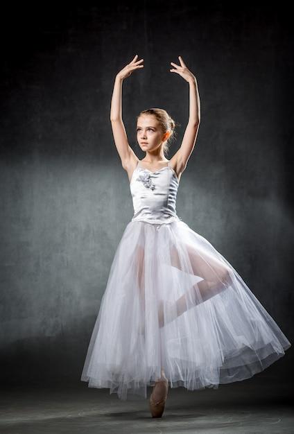 Een jonge en ongelooflijk mooie ballerina poseert en danst in een studio vol licht. fotografie weerspiegelt grotendeels de onvergelijkbare schoonheid van klassieke balletkunst. Premium Foto