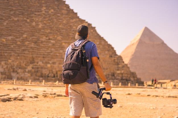 Een jonge fotograaf bij de piramide van cheops de grootste piramide. de piramides van gizeh zijn het oudste grafmonument ter wereld. in de stad caïro, egypte Premium Foto