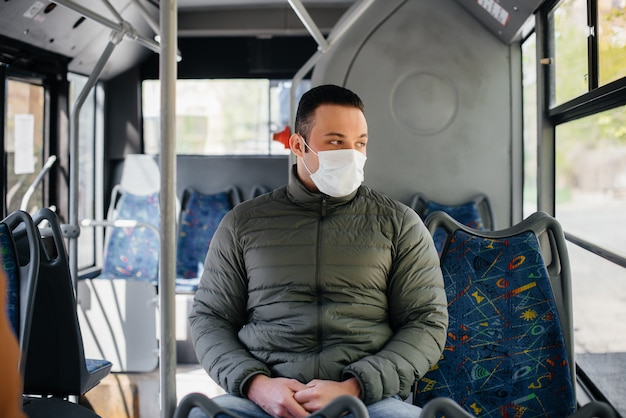 Een jonge gemaskerde man maakt alleen gebruik van het openbaar vervoer tijdens een pandemie. bescherming en preventie covid 19. Premium Foto