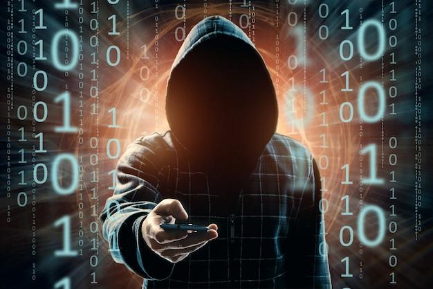 Een jonge hacker met capuchon hackt een smartphone, een hackeraanval, een silhouet van een man, gemengde media Premium Foto
