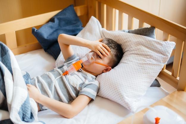 Een jonge jongen krijgt een inhalatie tijdens een longziekte. covid19, coronavirus, pandemie. Premium Foto