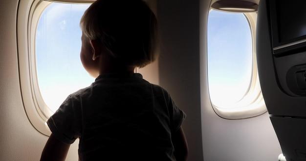 Een jonge jongenszitting op de zetel die uit een vliegtuigvenster kijkt terwijl het vliegen Premium Foto