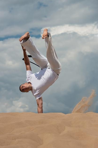 Een jonge kerel traint capoeira tegen de hemel. een man voert een acrobatische truc uit Premium Foto