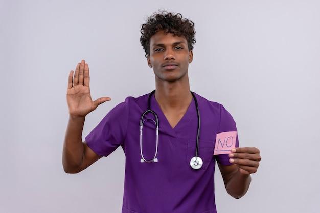 Een jonge knappe donkere mannelijke arts met krullend haar draagt een violet uniform met een stethoscoop en toont een papieren kaart met het woord nee Gratis Foto