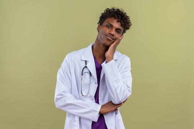 Een jonge knappe donkerhuidige man met krullend haar, gekleed in een witte jas met een stethoscoop die pijn voelt terwijl hij zijn tanden aanraakt op een groene ruimte Gratis Foto