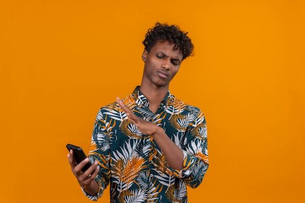 Een jonge knappe donkerhuidige man met krullend haar in een shirt met bladerenprint en een ontevreden uitdrukking op zijn mobiele telefoon Gratis Foto