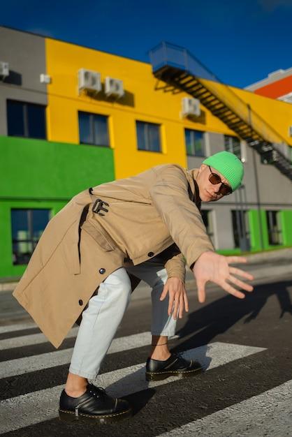 Een jonge knappe man in vintage bruine jas met in een stijlvolle groene hoed poseren buiten in de buurt van een moderne kleurrijke gebouwen. Premium Foto