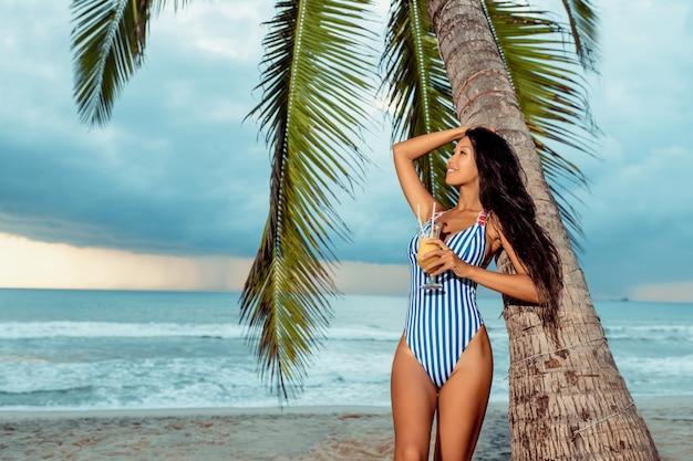 Een jonge luxe meisje in een bikini en staat met een glas sinaasappelsap onder een palmboom op een tropisch strand. Premium Foto