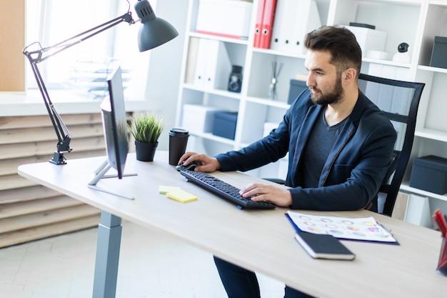 Een jonge man aan het werk in het kantoor op de computer. Premium Foto