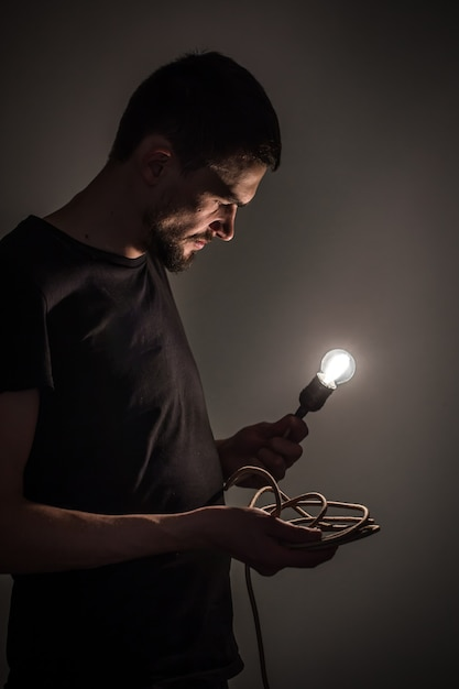 Een jonge man die een brandende gloeilamp in de hand houdt op zwarte achtergrondconceptenideeën Gratis Foto