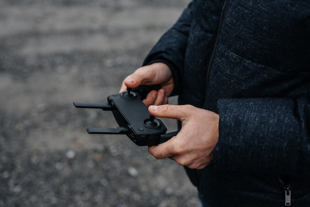 Een jonge man heeft een afstandsbediening voor het besturen van een helikopter. Premium Foto