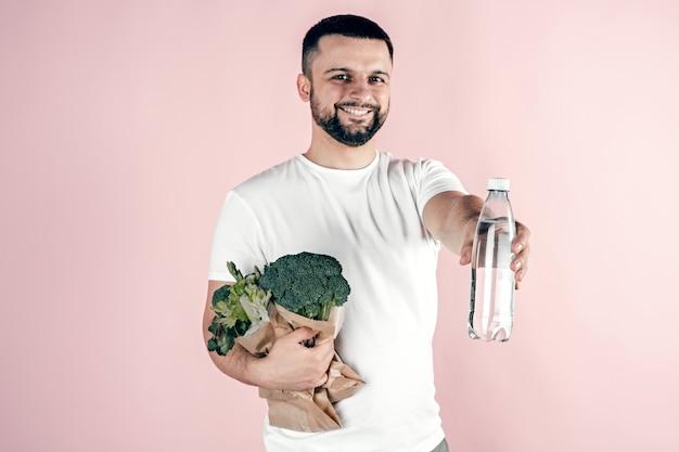 Een jonge man heeft een papieren zak met groenten en een fles water in zijn handen. gezond eten, vegetarisch. Premium Foto