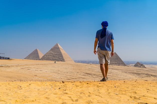 Een jonge man in een blauwe tulband loopt langs de piramides van gizeh, het oudste grafmonument ter wereld. in de stad caïro, egypte Premium Foto