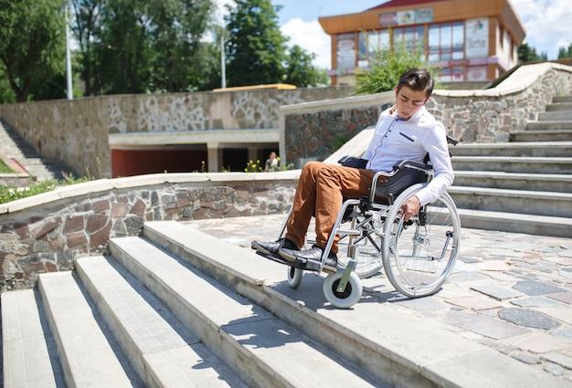 Een jonge man in een rolstoel die niet de trap af kan. Premium Foto
