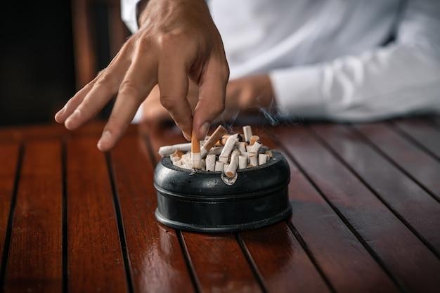Een jonge man in een wit overhemd houdt een sigaret in zijn handen en slaat hem in een asbak vol sigaretten. Premium Foto