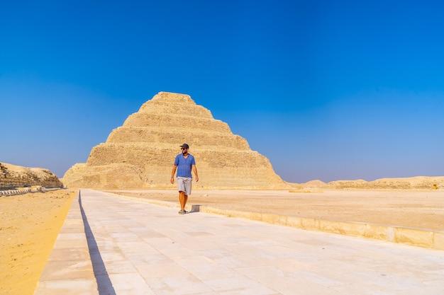 Een jonge man loopt in de getrapte piramide van djoser, saqqara. egypte. de belangrijkste necropolis in memphis. de eerste piramide ter wereld Premium Foto