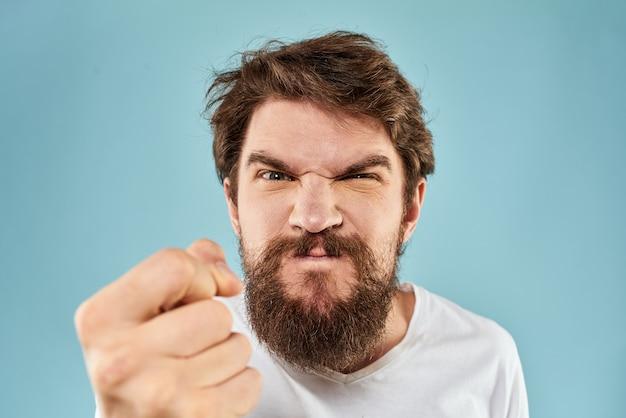 Een jonge man met een baard in een t-shirt toont verschillende emoties, plezier, verdriet, woede in de studio op de achtergrond Premium Foto