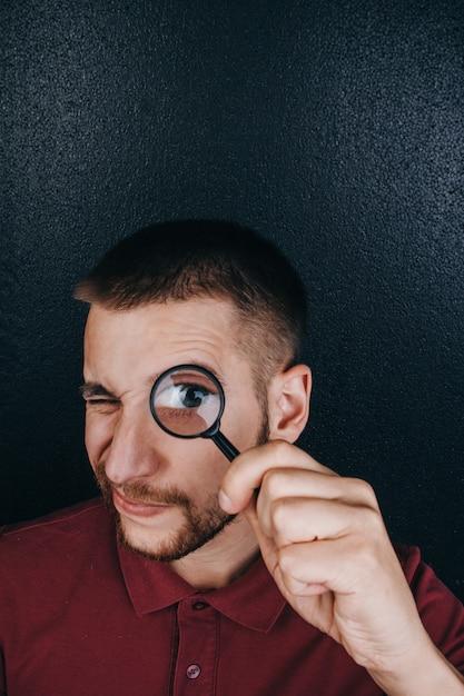 Een jonge man met een baard kijkt door een vergrootglas. Premium Foto