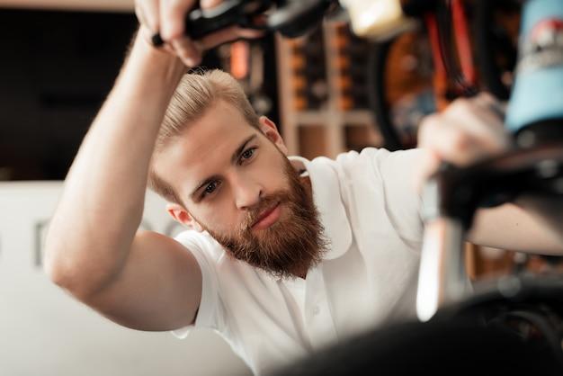 Een jonge man met een baard kijkt naar de details van de fiets Premium Foto
