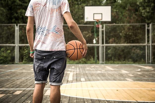 Een jonge man met een basketbal op het veld, het concept van sport Gratis Foto