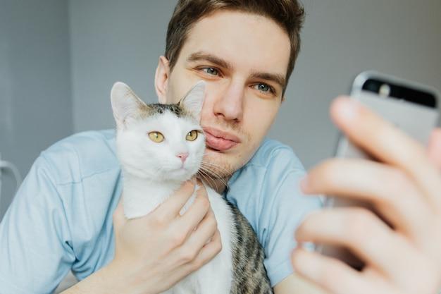 Een jonge man met een kat praten over een video-uitzending, communicatie. quarantaine Premium Foto