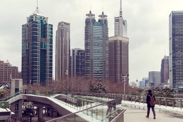 Een jonge man met een rugzak loopt op een zebrapad Premium Foto