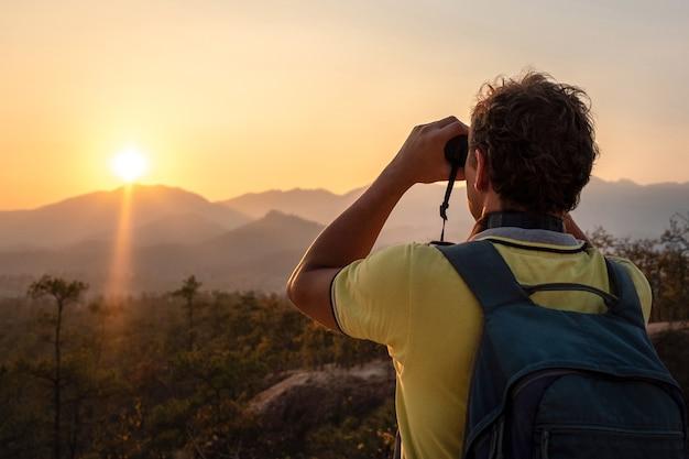 Een jonge man met een rugzak op zijn rug kijkt door een verrekijker naar de zonsondergang naar de silhouetten van de bergen. Premium Foto