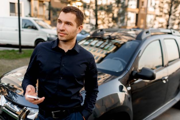 Een jonge man of zakenman in een donker overhemd staat op straat bij de auto, kijkt in de verte in een woonwijk van de stad. de chauffeur wacht op zijn passagier of klant. Premium Foto