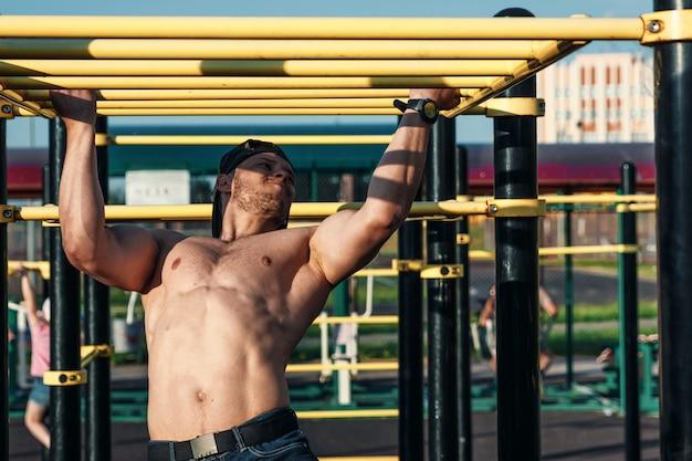 Een jonge man trekt zich omhoog op het sportveld, een atleet traint buiten in de stad Premium Foto