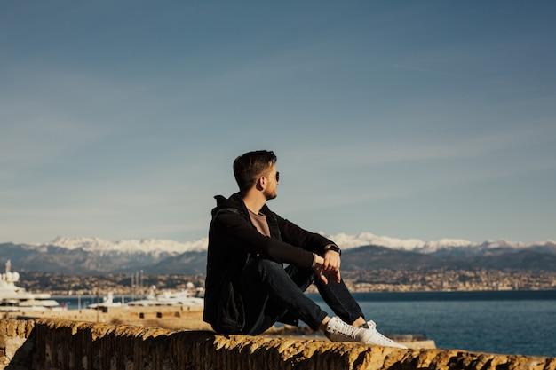Een jonge man zit aan de waterkant en genietend van het uitzicht op zee. Premium Foto