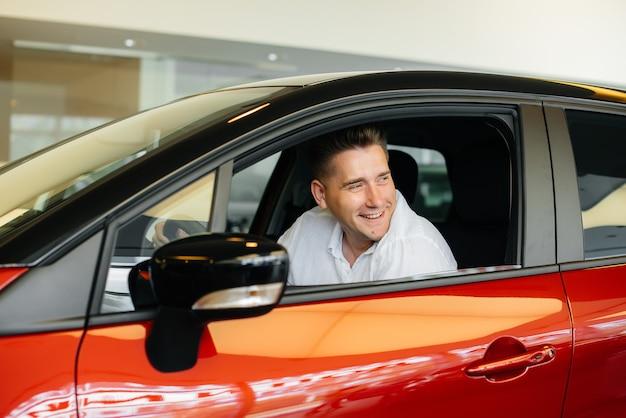 Een jonge man zit in de cabine van een nieuwe auto en test hem. een auto kopen. Premium Foto