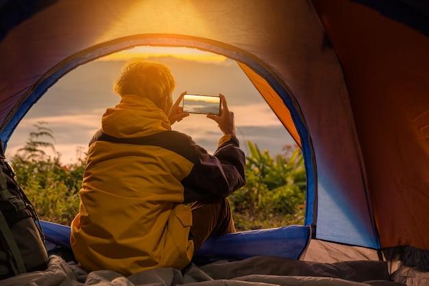 Een jonge man zit in de tent met het nemen van foto met een mobiele telefoon Gratis Foto
