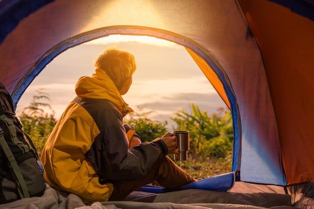 Een jonge man zit in de tent met koffiekopje te houden Gratis Foto