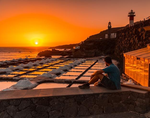 Een jonge man zit in de zonsondergang van de fuencaliente-vuurtoren naast de zoutmijn, op de route van de vulkanen ten zuiden van het eiland la palma, canarische eilanden, spanje Premium Foto