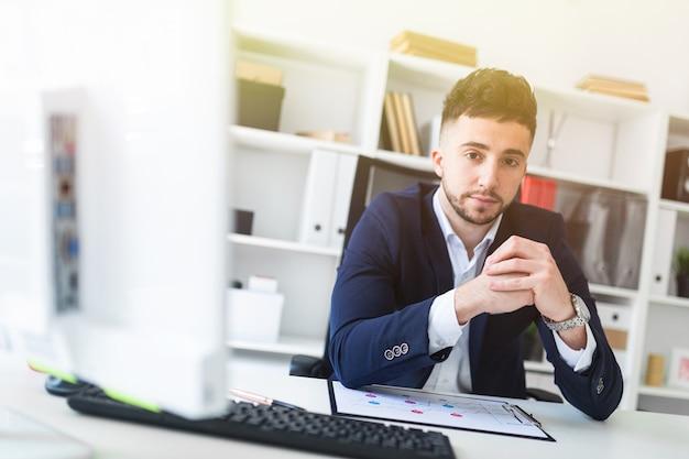 Een jonge man zit op kantoor op een computer bureau en werken met documenten. Premium Foto