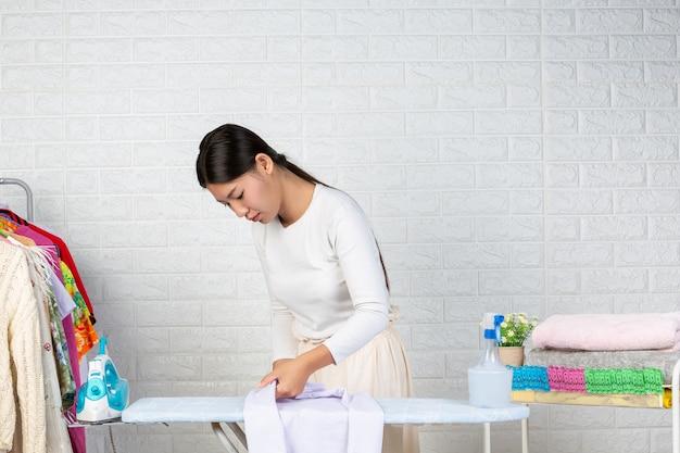 Een jonge meid die een shirt op haar strijkplank met een witte baksteen aan het voorbereiden is. Gratis Foto