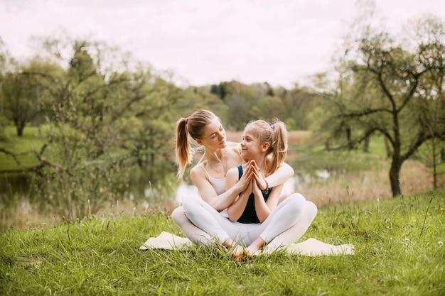 Een jonge moeder en dochter in sportkleding doen samen yoga in een park Premium Foto