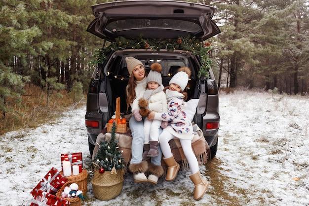 Een jonge moeder en twee kleine meisjes zitten in de kofferbak van een auto Premium Foto