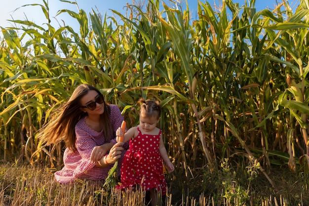 Een jonge moeder met een kind dat bij een grootmoeder en grootvader op een boerderij rust. Premium Foto