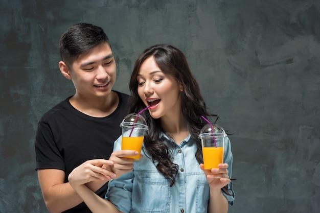 Een jonge mooie aziatische paar met een glas sinaasappelsap Gratis Foto