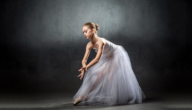 Een jonge mooie ballerina poseert in de studio. een kleine danser. ballet. Premium Foto