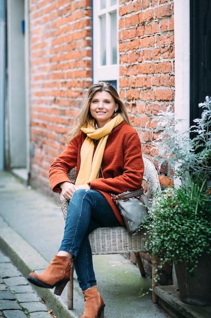Een jonge mooie blonde vrouw zit als voorzitter en geniet van kleine stedelijke straat in lübeck. Premium Foto