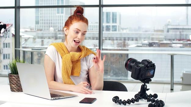 Een jonge mooie meisjesblogger neemt haar blog op een digitale camera op Premium Foto