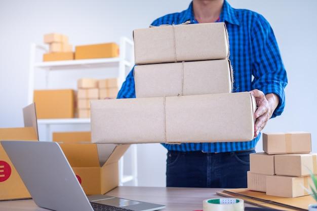 Een jonge ondernemer met een doos om producten naar klanten te sturen. online verkopers accepteren bestellingen via de website. klein familiebedrijf, e-commerce concept Premium Foto